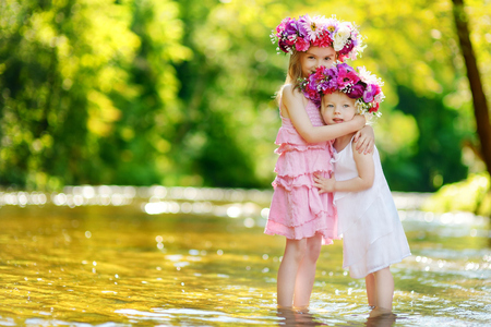 coronet: Two adorable little sisters wearing flower crowns by a river on warm and sunny summer day