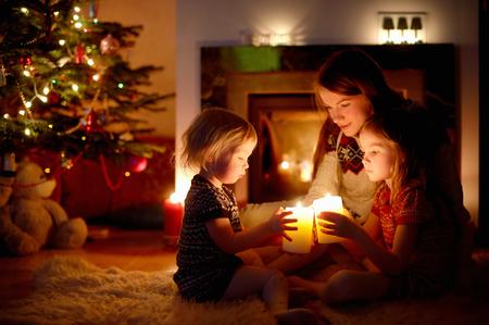 젊은 어머니와 크리스마스 이브에 아늑한 어두운 거실에 촛불을 들고 벽난로 옆에 앉아 그녀의 두 어린 딸