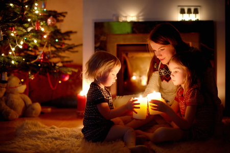 fireplace living room: Young mother and her two little daughters sitting by a fireplace holding candles in a cozy dark living room on Christmas eve Stock Photo