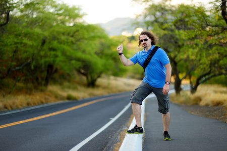 hitchhiking: Young tourist with a backpack hitchhiking along a road Stock Photo