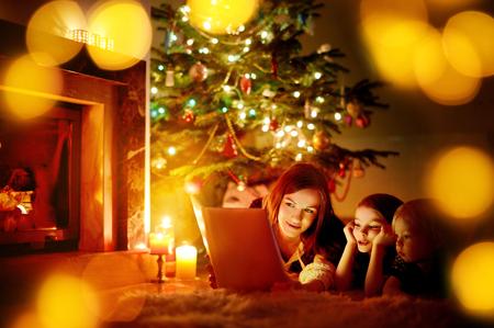 Jonge moeder en haar twee dochtertjes het lezen van een boek van een kerstboom in de gezellige woonkamer in de winter Stockfoto