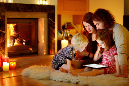 home decorated: Happy young family using a tablet pc at home by a fireplace in warm and cozy living room on winter day