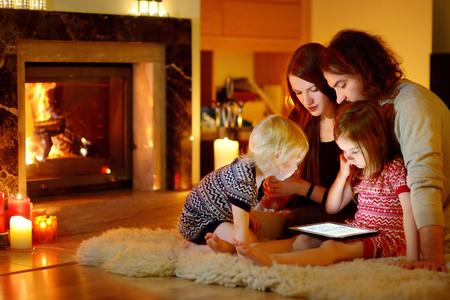 Mladá rodina s použitím tablet pc doma u krbu v teplé a útulné obývacím pokoji na zimní den