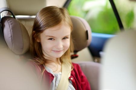 安全に車の座席に座っているかわいい女の子 写真素材