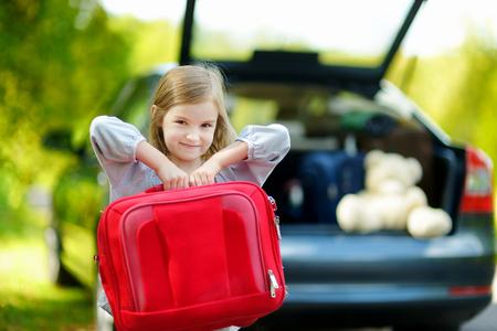 maleta: Niña adorable con una maleta dejando para un coche vacaciones con sus padres