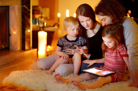 comfortable home: Happy young family using a tablet pc at home by a fireplace in warm and cozy living room on winter day