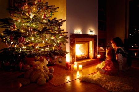 decorated christmas tree: Young mother and her daughter by a fireplace on Christmas