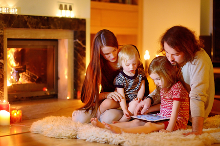 fireplace family: Happy young family using a tablet pc at home by a fireplace in warm and cozy living room on winter day