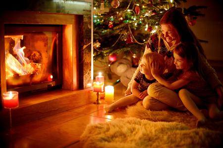 camino natale: Giovane madre e le sue due piccole figlie, seduta da un camino in un accogliente soggiorno buio alla vigilia di Natale