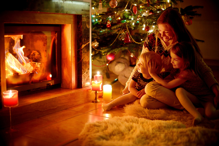 fireplace living room: Young mother and her two little daughters sitting by a fireplace in a cozy dark living room on Christmas eve