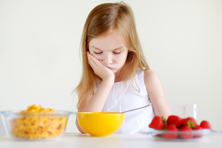 comiendo cereal: Adorable little girl eating cereal with strawberries in white kitchen