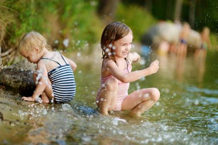 bebe sentado: Dos pequeñas hermanas vistiendo trajes de baño que se divierten en un río en verano
