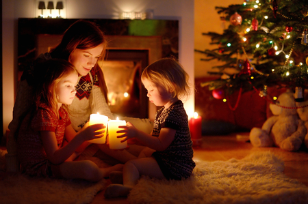 Jonge moeder en haar twee kleine dochters zitten bij een open haard met kaarsen in een gezellige donkere woonkamer op kerstavond Stockfoto