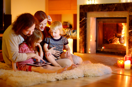 겨울 날에 따뜻하고 아늑한 거실에 벽난로가 집에서 태블릿 PC를 사용하는 행복 한 젊은 가족