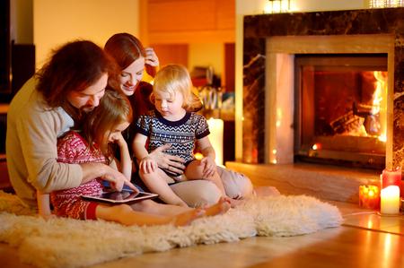 usando computadora: Familia de joven feliz usando un Tablet PC en su casa por una chimenea en el c�lido y acogedor sal�n el d�a de invierno
