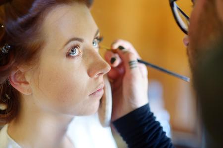 mujer maquillandose: Joven novia hermosa aplicación de maquillaje de la boda por el artista de maquillaje profesional