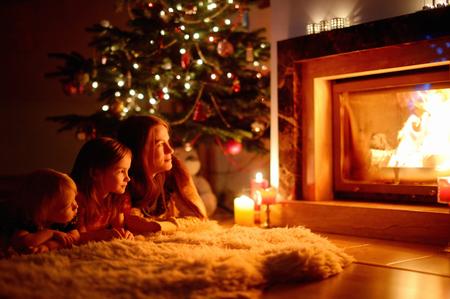 젊은 어머니와 크리스마스 이브에 아늑한 어두운 거실에서 벽난로 옆에 앉아 그녀의 두 작은 딸 스톡 콘텐츠