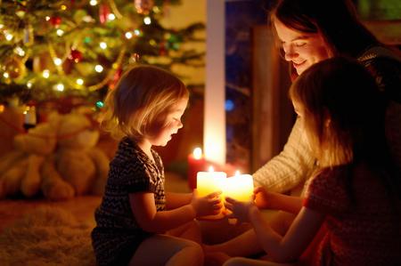 Joven madre y sus dos pequeñas hijas que se sientan por una chimenea con velas en una acogedora sala de estar oscuro en la víspera de Navidad