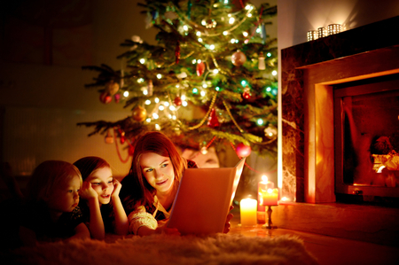 fireplace family: Young mother and her two little daughters reading a book by a Christmas tree in cozy living room in winter