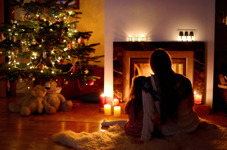 traditional christmas: Young mother and her daughter by a fireplace on Christmas
