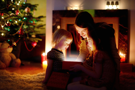 Young mother and her two little daughters opening a magical Christmas gift by a Christmas tree in cozy living room in winter Banque d'images