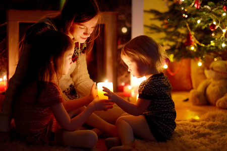 Young mother and her two little daughters sitting by a fireplace holding candles in a cozy dark living room on Christmas eve Stock Photo