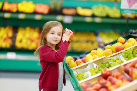 produce departments: Little girl choosing a bio apple in a store