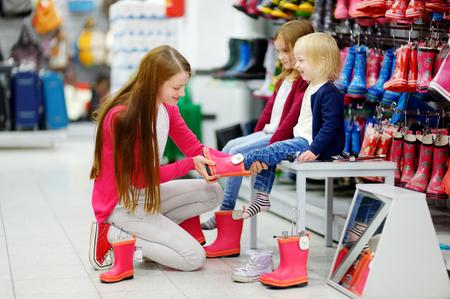 Jonge moeder en haar twee kleine meisjes kiezen en proberen op nieuwe regen laarzen in een supermarkt
