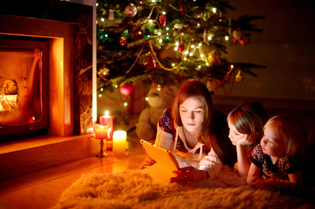 family movies: Young mother and her daughters using a tablet pc by a fireplace on warm Christmas evening