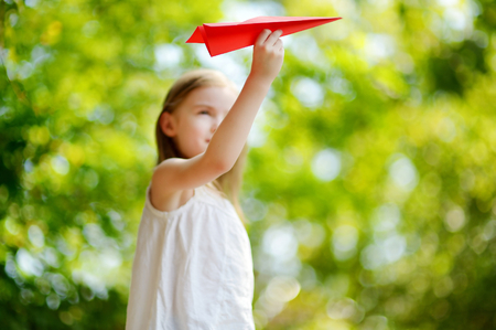 Adorable little girl holding a paper plane outdoors on sunny summer day