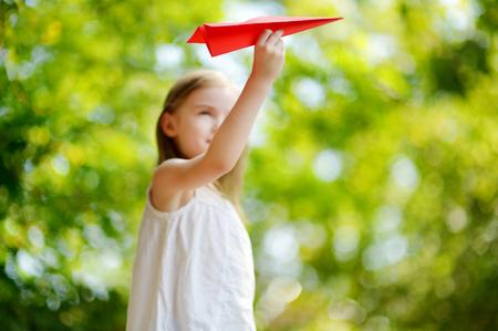 Niña adorable que sostiene un avión de papel al aire libre en día soleado de verano