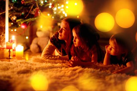 젊은 어머니와 크리스마스 이브에 아늑한 어두운 거실에 벽난로 옆에 앉아 그녀의 두 어린 딸