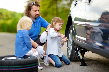 two wheel: Young father and his two daughters changing a car wheel outdoors on beautiful summer day