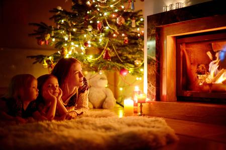 Jonge moeder en haar twee kleine dochters zitten bij een open haard in een gezellige donkere woonkamer op kerstavond Stockfoto