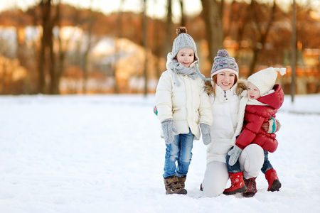cute babies: Joven madre y sus dos hijas que se divierten el d�a de invierno Foto de archivo