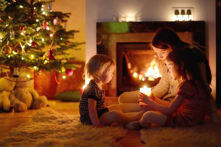 젊은 어머니와 그녀의 두 작은 딸 크리스마스 이브에 아늑한 어두운 거실에서 촛불을 들고 벽난로 옆에 앉아