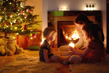 Jonge moeder en haar twee kleine dochters zitten bij een open haard met een kaars in een gezellige donkere woonkamer op kerstavond Stockfoto