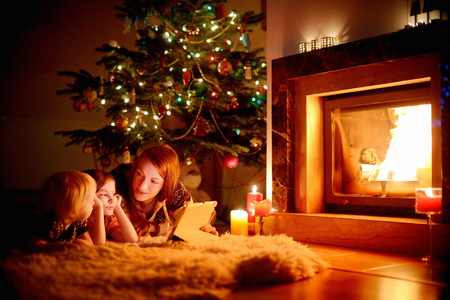 Young mother and her daughters using a tablet pc by a fireplace on warm Christmas evening
