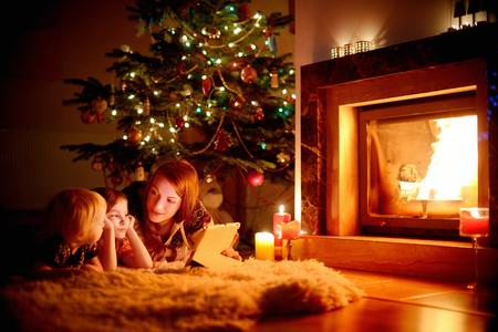 Jonge moeder en haar dochters met behulp van een tablet-pc door een open haard op warme kerst avond Stockfoto