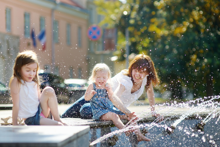 hot water tap: Young woman and two little kids having fun by a city fountain on hot and sunny summer day