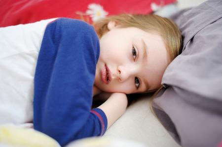 naptime: Little preschooler girl in bed on sunny morning