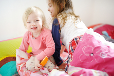 naptime: Two little sisters playing in bed on sunny morning