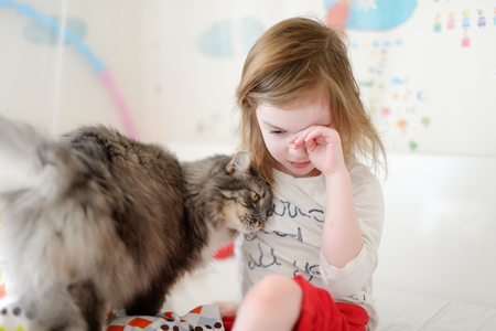 naptime: Little preschooler girl in pajamas and her cat on sunny morning