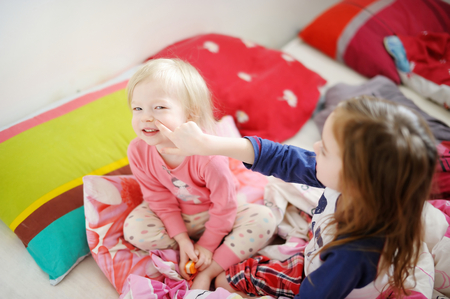 Two little sisters playing in bed on sunny morning