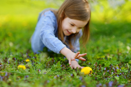 fiori pasqua: Adorable little girl hunting for easter egg in blooming spring garden on Easter day