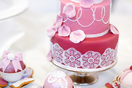 White wedding cake decorated with pink sugar flowers photo