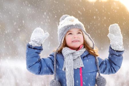 Drôle de petite fille amusant dans un beau parc d'hiver pendant les chutes de neige Banque d'images
