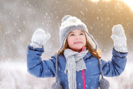 balls kids: Funny little girl having fun in beautiful winter park during snowfall