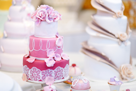 wedding table decor: White wedding cake decorated with pink sugar flowers