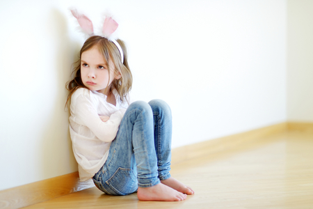 Very angry little girl wearing bunny ears sitting on a floor at home 스톡 콘텐츠